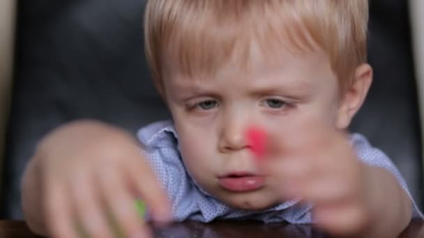 Smutný malý chlapec hraje s barevnými Plastelíny.