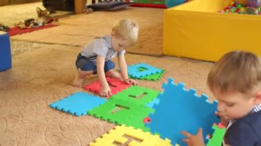 Two small children play with large soft puzzle.