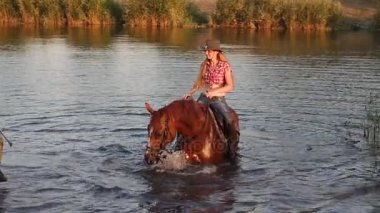 Girl with a horse swim in a small lake at sunset.