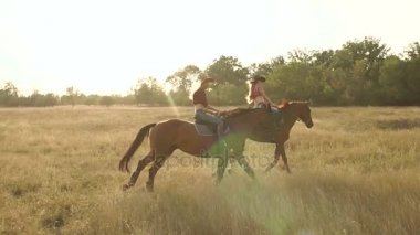 Two girls riding horses in field at sunset.
