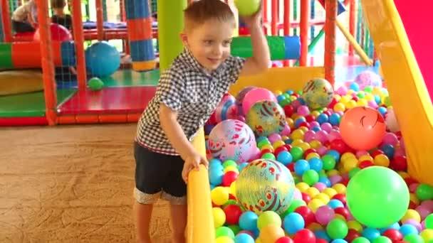 Kleiner Junge spielt auf einem bunten Spielplatz.