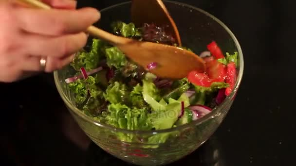 Detail dívky mísí zeleninový salát na černém pozadí