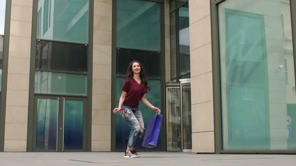 Dívka, která skočila pro radost s nákupní tašku v ruce
