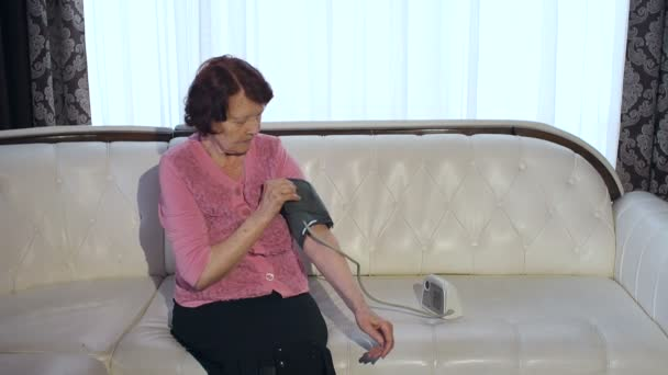 Oma misst zu Hause den Blutdruck.
