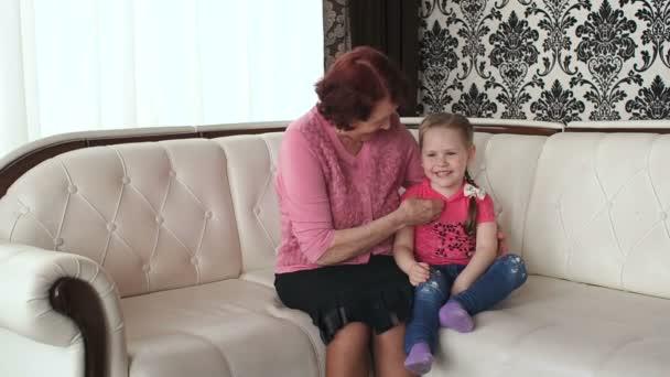 Grandma tickles her granddaughter