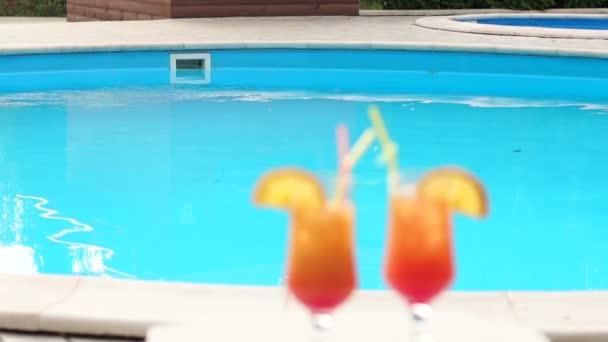 Dva rozmazané sklo s koktejlem u bazénu.