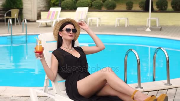 Sexy girl sitting on lounger and drinking cocktail