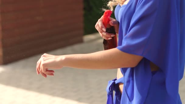 Close-up of a girl sprays on your hands sunscreen.