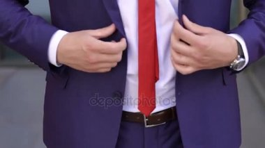 Businessman buttoning jacket, close-up.