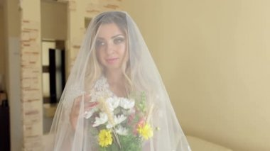 Portrait of a bride in wedding veil with a flowers
