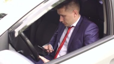 Close-up of man sitting with the phone in the car.