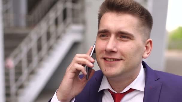 Portrét obchodníka s telefonem venku.