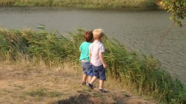 Two boys throw stones into the lake in summer day.