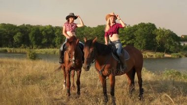 Two sexy girls riding horses at sunset in a field.