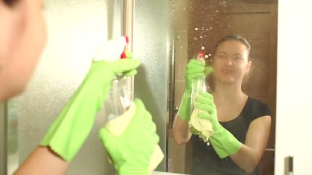 Nő tisztítja a permetezőpalack fürdőszoba tükör.