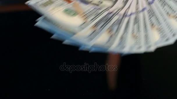 Muž dává hromadu sto dolarové bankovky na stole