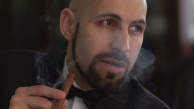 Elegant man in a suit smoking a cigar, slow motion