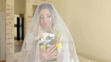 Portrait of bride with flowers and a veil at home.