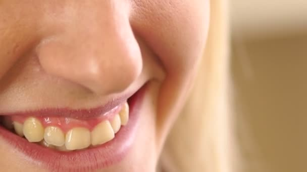 Beautiful blonde girl smiling, showing her teeth.