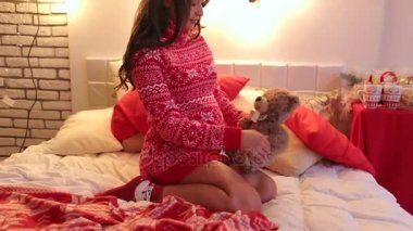 Pregnant woman sitting on bed with Teddy bear.