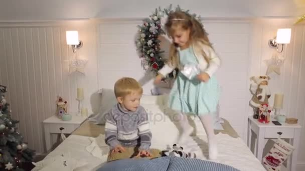 Two children jumping on the bed for Christmas.