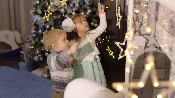 Zwei kleine Kinder spielen in der Nähe von the Christmas tree