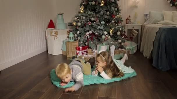 Zwei Kinder liegen neben Weihnachtsbaum auf dem Boden.