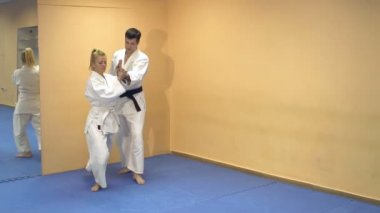 Man and woman demonstrate the technique Aikido.
