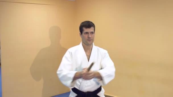A fiatalember Aikido gyakorlása a tornateremben.