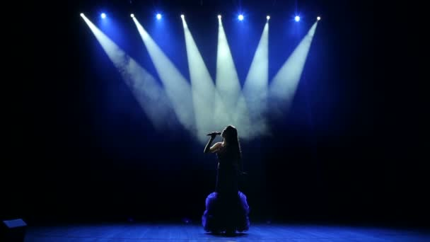 Fiatal nő, színes fények énekel a koncert.