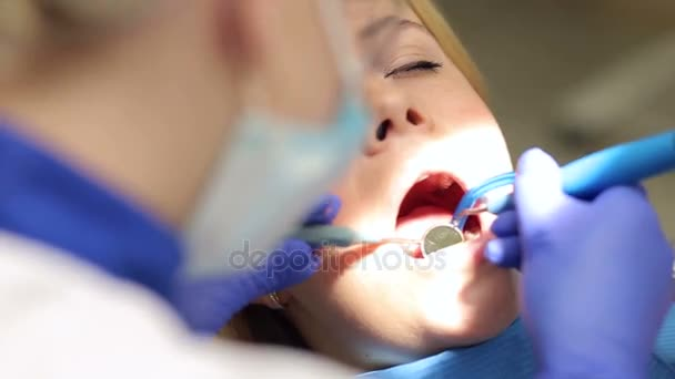 Dental treatment of young woman at dentist office.