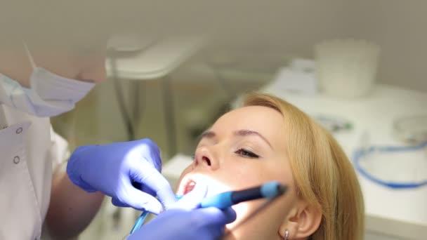 Zubař léčí zuby dívky v klinice.