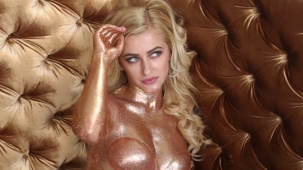 Close-up sexy Nude girl with a Golden shiny skin.