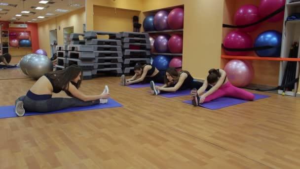 Skupina čtyř dívek dělá strečink v tělocvičně