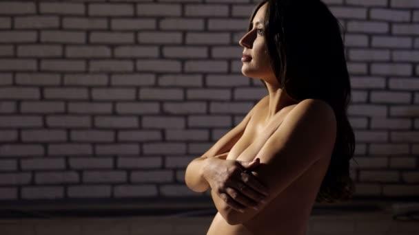 A sötétben meztelen terhes lány portréja.