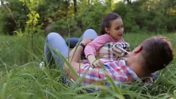 Táta baví s dětmi na trávě v parku