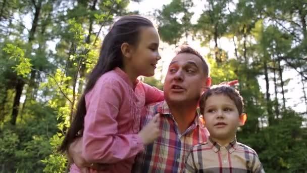 Šťastný otec objímá jeho děti v parku