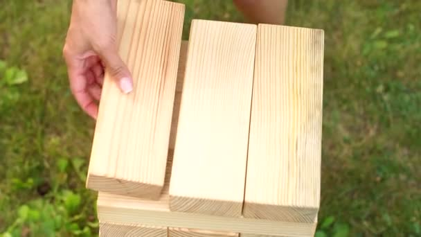Young girl building a tower of jenga in the Park.