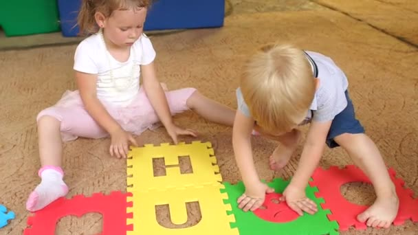 Group of children play with a large soft puzzle.