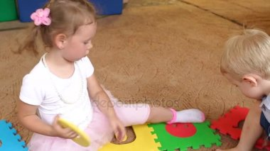 Two small children play with a large soft puzzle.