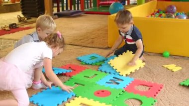 Small children collect the puzzle with alphabet.