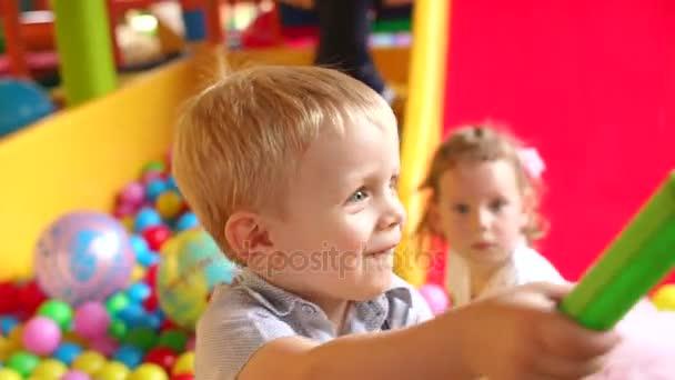 Dvě veselé děti si hrají na dětském hřišti