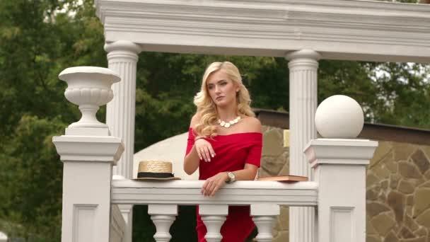 Piros ruhás lány támaszkodva a lépcső korlát.