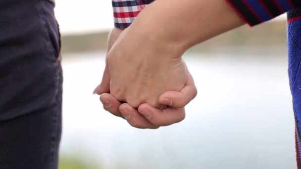 Lovers holding hands in nature close-up.