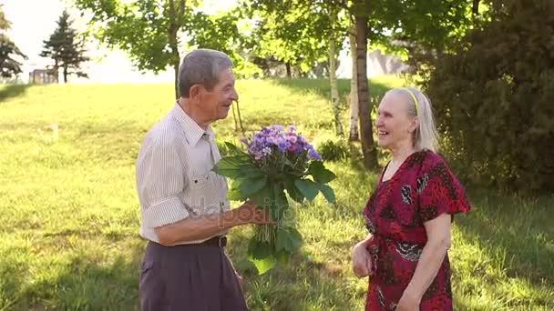 Uomo anziano dà i fiori alla sua amata moglie nel parco