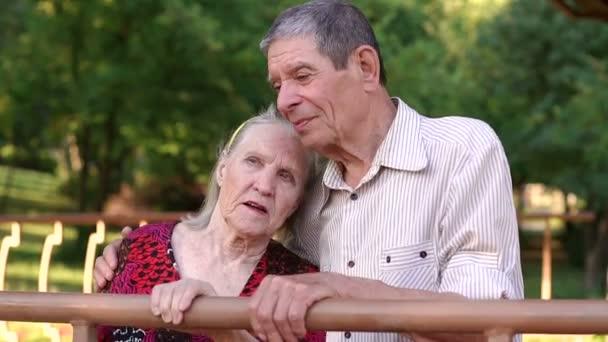 Stará babička a děda jsou objímání v parku.