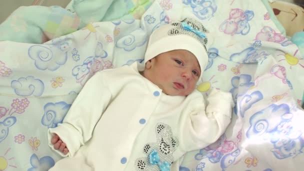 Detail o novorozeně v bílém klobouku leží na posteli