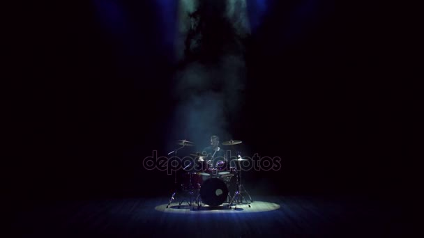 Man playing drums on black background with smoke.
