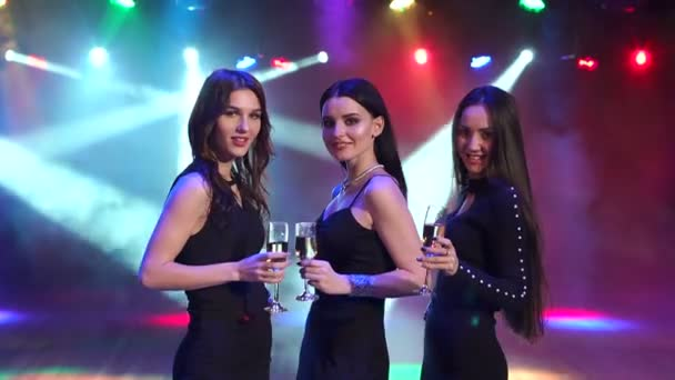 Three happy girls with champagne at a nightclub.
