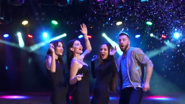Friends dancing in nightclub with falling confetti